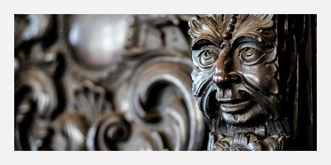 Museu da Misericórdia - Detalhe de um móvel de madeira com um rosto – olhos, nariz e boca.