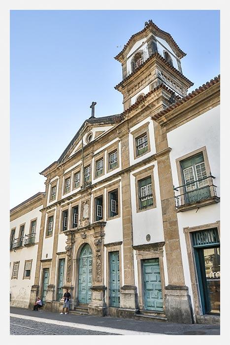 Museu da Misericórdia - Fachada do Museu da Misericórdia com portas e janelas verdes, uma cruz no topo e um sino na torre mais alta