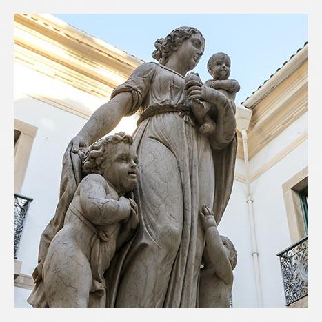Museu da Misericórdia - Imagem destaca a Estátua da Caridade, obra representada por uma mulher em pé, com uma criança no colo e duas ao seu redor.