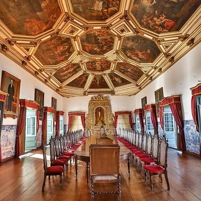 Museu da Misericórdia - Vista do Salão Nobre do Museu com mesa grande e mais de vinte cadeiras de madeira ao redor, teto com telas pintadas a mão e um cristo na cruz ao fundo