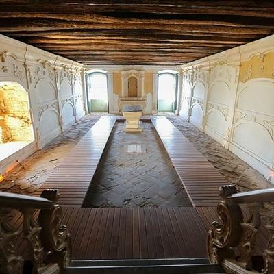 Museu da Misericórdia - Fotografia do ossuário do museu, localizado no subsolo, a partir de uma escada, com duas janelas ao fundo por onde entra raios do sol, paredes brancas e uma estrutura de madeira ao centro